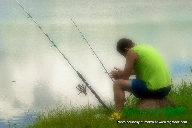Photo of a man fishing on the river bank